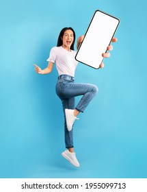 Advertisement for mobile application. Excited young lady jumping over blue studio background, showing modern smartphone with empty screen, mockup for app. Collage - Shutterstock ID 1955099713