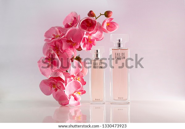 Advertisement of parfum: bottles with pinck orchid flowers on a pinky white background with reflections. Artificial flowers.