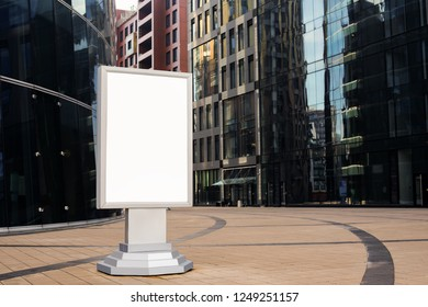Advertising billboard with blank display with copy space background for public information standing near buildings with contemporary exterior. Blank banner with empty screen standing near enterprise