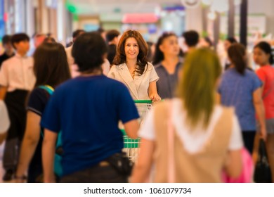 Advertising, Business Concept - Asian woman pushing shopping cart in shopping mall and Blurred image of people in shopping mall. ( lens blur effect )
