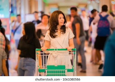 Advertising, Business Concept - Asian woman walking and pushing shopping cart in shopping mall with Blurred shopping mall background. ( lens blur effect )