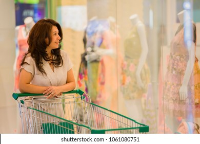 Advertising, Business Concept - Asian woman pushing shopping cart in shopping mall and Blurred image of clothes display in the fashion store. ( lens blur effect )