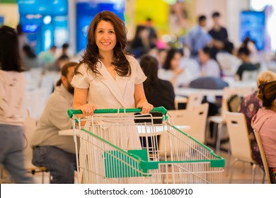 Advertising, Business Concept - Asian woman pushing shopping cart in shopping mall and Blurred image of people in food court. ( lens blur effect )