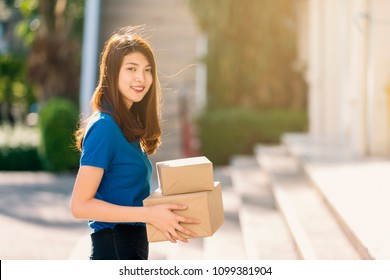 Advertising, Business Concept - The best delivery service. Beautiful Delivery asian woman in blue uniform holding cardboard box outdoor and leave space for adding your content. (vintage color tone)