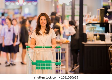 Advertising, Business Concept - Happy Asian woman pushing trolley in shopping mall and Abstract blur shopping mall and retail store interior for background. ( lens blur effect )