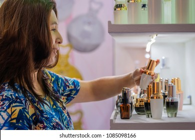Advertising, Business, Cosmetics, Beauty Concept - Asian woman stands at the Cosmetic glass bottle shelf. Different color of packages and Blank packaging cosmetic template for your design on shelf.