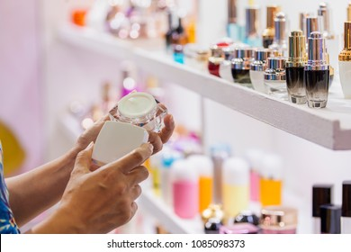 Advertising, Business, Cosmetics, Beauty Concept- Woman picking blank packaging white cosmetic cream pot with cap from shelf in store on Blur background Different of Cosmetics packages design product.