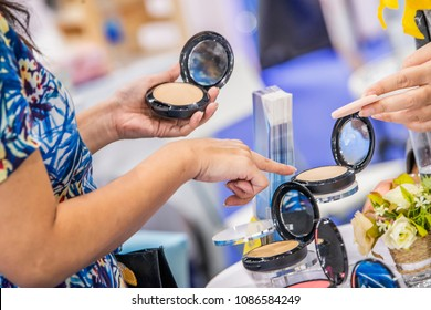 Advertising, Business, Cosmetics, Beauty Concept - Woman' s hand holding face powder in a black container and choosing face powder at cosmetic boutique, testing before buying. Shopping for cosmetics.