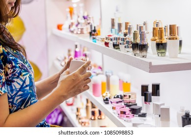 Advertising, Business, Cosmetics, Fashion, Beauty Concept - Cosmetics Packages design Beauty Products. Woman picking blank packaging white cosmetic cream pot with cap from shelf in cosmetics store.