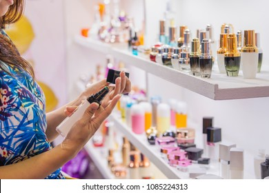 Advertising, Business, Cosmetics, Fashion, Beauty Concept - Woman buying beauty product package and testing Cosmetic plastic bottle with dispenser pump for gel, lotion, cream, shampoo, bath foam.