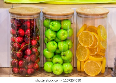 Advertising, Business, Food Concept - Interior design with colorful decorative glass bottles. Fake fruit, Green apple, Cherry, Lemon in glass jars. Food model for shop presentation. Select focus