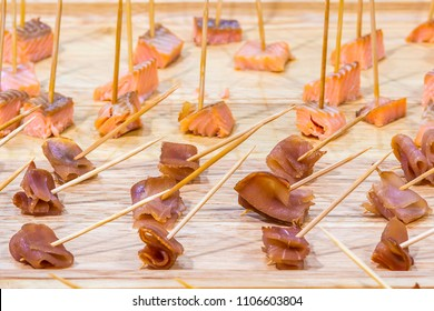 Advertising, Business, Food, Health Concept - Offering food samples to customers in shop. Smoked tuna and Smoked salmon on a wooden stick. Select focus