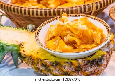 Advertising, Business, Fruit Concept - Dry pineapple as tasty snack. Candied dried pineapple in the bowl on the half of pineapple. Selective focus