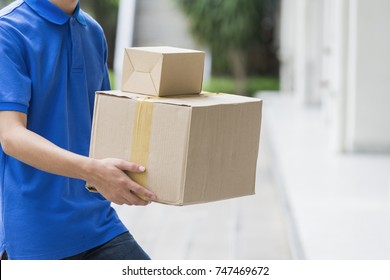 Advertising, Business, Transportation Concept - Delivery man holding pile of cardboard boxes in front with copy space. Selective Focus