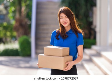 Advertising, Business, Transportation, Delivery Concept -  The best delivery service. Beautiful Delivery asian woman holding pile of cardboard boxes in front while standing against residential house.
