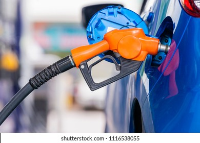 Advertising, Business, Transportation, Technology, Energy Concept - Gas nozzle pumping gas into a blue car to fill the machine with fuel at Gas station and leave space for adding your content.