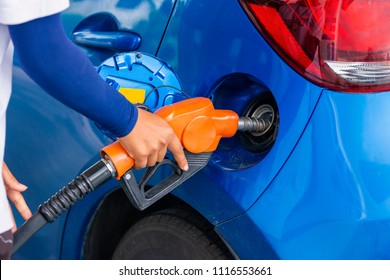 Advertising, Business, Transportation, Technology, Energy Concept - Gas station attendant at work. Woman' hand pumping gasoline fuel in blue car at gas station. Select focus