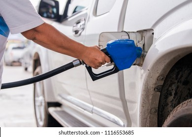 Advertising, Business, Transportation, Technology, Energy Concept - Man fills up his car with a gasoline at gas station. White pickup truck refueling at gas station. Select focus
