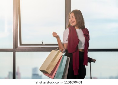 Advertising, Business, Travel, Shopping Concept - Asian woman standing at the window in airport terminal and walking in the airport while carrying suitcase, shopping bags, passport and boarding pass.