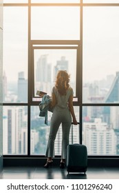 Advertising, Business, Travel,Shopping,Fashion Concept- Vertical shot of Beautiful woman looking through the window in airport while carrying suitcase, passport and boarding pass. Start of her journey