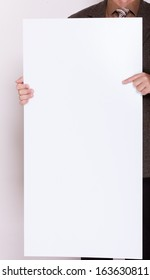 Advertising concept. Businessman holding blank sign empty billboard pointing space for text. Male hands with white banner.