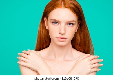 Advertising concept. Close-up portrait of nice perfect nude calm red-haired girl with shiny pure clean fresh smooth flawless skin, embracing herself, isolated over green turquoise background