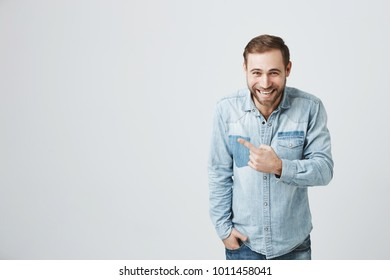 Advertising concept. Excited cheerful european man wearing denim shirt expressing positive emotions, laughing at camera, pointing index finger at copy space, motivating and attracting customers.