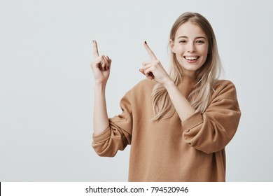 Advertising concept. Excited cheerful european woman with long blonde hair, wearing casual clothes and smiling happily, pointing index fingers upwards, motivating and attracting customers.