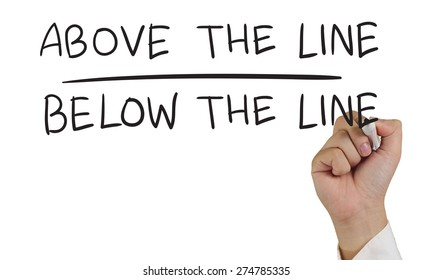 Advertising concept image of a hand holding marker and write Above and Below The Line isolated on white