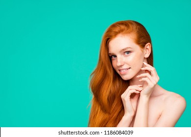 Advertising concept. Portrait of nice cute nude tender sweet gentle red-haired girl with shiny pure clean skin and healthy hair, touching cheek, copy-space, isolated over green turquoise background