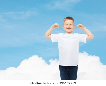advertising, dream, people and childhood concept - smiling little boy in white blank t-shirt with raised hands over sky background
