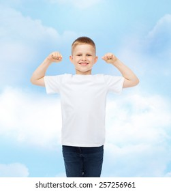 advertising, dream, people and childhood concept - smiling little boy in white blank t-shirt with raised hands over cloudy sky background