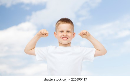 advertising, ecology, people and childhood concept - smiling little boy in white blank t-shirt flexing biceps over blue sky background