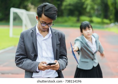 Advertising, Education, Business, Technology Concept - Asian Businessman are addicted using mobile phone and doesn't want to work.