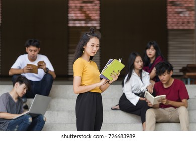 Advertising, Education Concept - Enjoying university life. Beautiful asian student reading book while standing in university with her friends reading book and using laptop in the background.