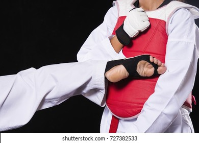 Advertising, Education Concept - Two young athletes are taekwondo fighters and taekwondo Fight Wrestling olympics on black background.
