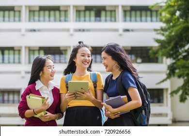 Advertising, Education Students People Knowledge Concept - Group of Beautiful Asian students talking together and checking on line content on Tablet with the university building in the background.