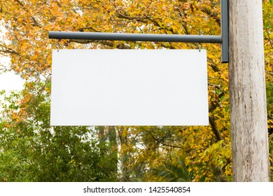 Advertising empty white blank board hanging on a wooden pole on the left, with nature forest in the background. Copy space available for text