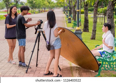 Advertising, Entertainment, Education Concept - Group of asian students photographer student taking pictures, learning creative portrait during photo shooting workshop course outdoor.