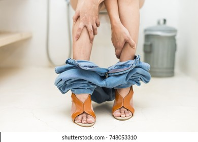 Advertising, Health concept - Woman wearing jeans and high heel shoes suffers from diarrhea is sitting on toilet bowl. Selective Focus