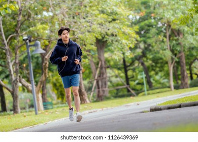 Advertising, Healthy, Lifestyle, Sport Concept - Starting day from morning jog. Full length shot of Young asian man runner jogging exercise in park, listening smartphone music and copy space.