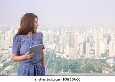 Advertising, Modern cityscape, Network, Technology Concept - Asian woman using a digital tablet while standing  outdoor on background blur building skyscrapers and leave space for adding your content.
