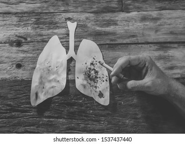 Advertising style picture of Tobacco and lung cancer, Medical warning, stop smoking and smoking kills campaign. conceptual image of hand with burning cigarette using lungs as ashtray.