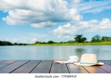 Advertising, Travel planning vacation concept - Holiday idea. Cup of coffee, Hat, Map on the edge of a wooden jetty. background blur beautiful sky with lake and leave space for adding your content.