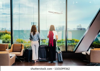 Advertising, Travel, Shopping Concept - Two friends traveling together. Young woman in the airport, looking through the window at planes waiting at boarding gate before departure with her suitcase.