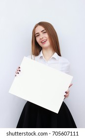 Advertising. Young business woman in white shirt and skirt showing blank board and smiling on white background