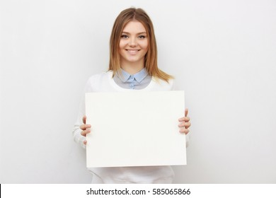 Advertising. Young smiling woman show blank board on white background.