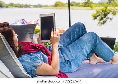 Advertising,Time to relax, Holiday, Technology, Education Concept - Asian woman an using a digital tablet computer while relaxing on sofa outdoor and background blur beautiful sky with lake.