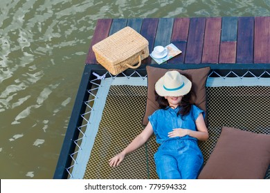 Advertising,Travel, Time to relax Concept - Lady feels tired, so she need time for relaxation. Top view of asian woman lying by the lake near the girl is suitcase, cup of coffee, map with copy space.