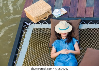 Advertising,Travel, Vacation, Time to relax Concept - Top view of Beautiful woman lying by the lake after work finished. Thinking, contemplation relaxing, concentration, loneliness with copy space.